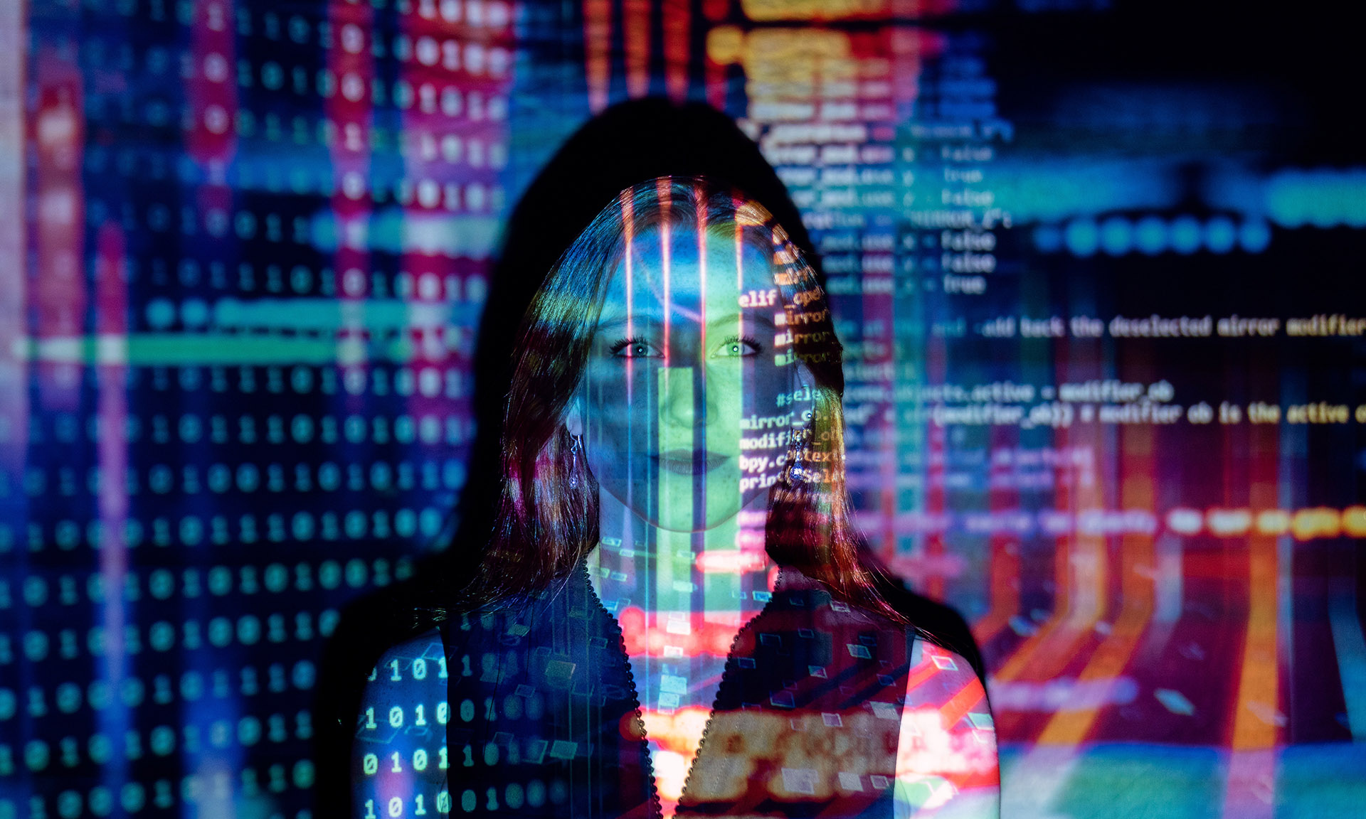 Young professional woman with computer code projected over her face and torso.